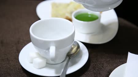 teabag : Pouring tea into white cup on table from porcelain kettle. jelly and pancake on a background
