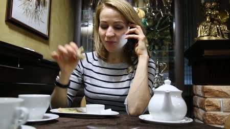 оладья : Woman eats delicious hot pancakes and talking on a phone