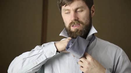 pólos : Businessman tying a tie on brown background Stock Footage
