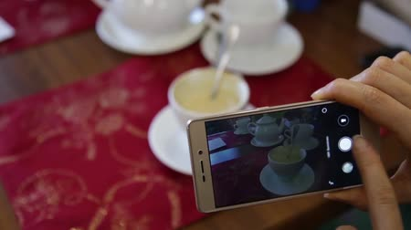 make photo : Trendy woman in a restaurant make photo of food with mobile phone camera for social network