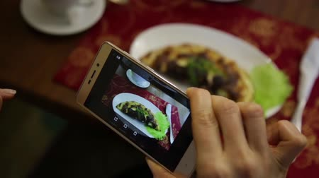 pic : Trendy woman in a restaurant make photo of food with mobile phone camera for social network