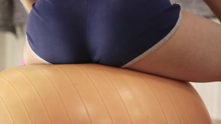 abs : Beautiful fitness woman with toned body sitting on the fitness ball and doing exercises. slow motion
