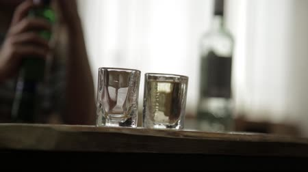 krk : man alone pouring and quickly drinking alcohol from two glasses. male alcoholism and depression