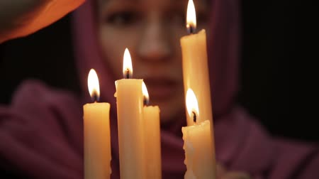 astrologist : woman doing the magic ritual. close-up several candle. halloween or religion concept
