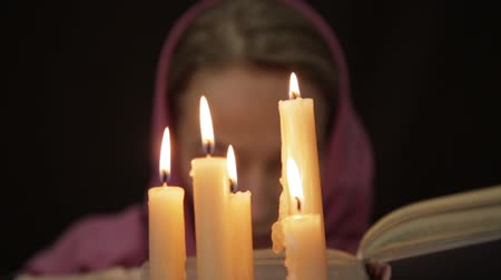 psicodélico : woman in a headscarf doing the magic ritual. close-up several candle and old book. halloween or religion concept Stock Footage