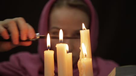 palmist : woman in a headscarf doing the magic ritual. close-up several candle and old book. halloween or religion concept Stock Footage