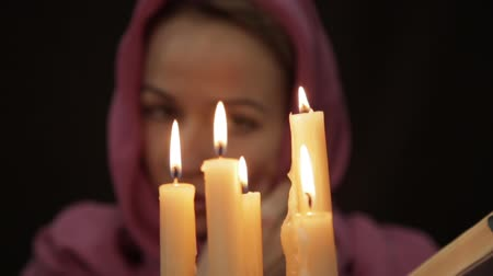 wicca : woman in a headscarf doing the magic ritual. close-up several candle and old book. halloween or religion concept Stock Footage
