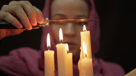 astrologist : woman in a headscarf doing the magic ritual. close-up several candle and old book. halloween or religion concept Stock Footage