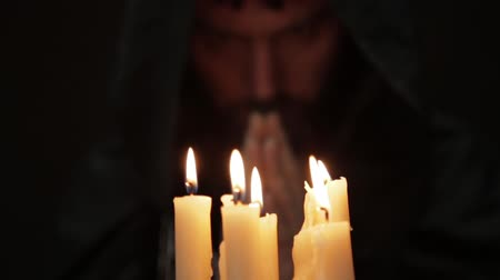astrologist : man doing the magic ritual. close-up several candle and old book. necromancer casts spells from thick ancient book by candlelight