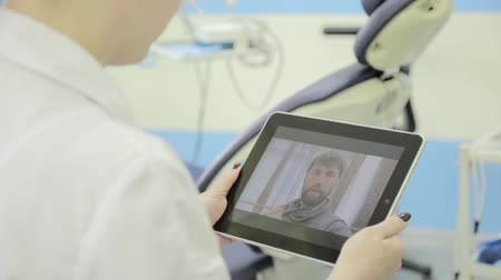 physicians : senior patient video chatting with dentist on pc tablet. On-line medical consultations.
