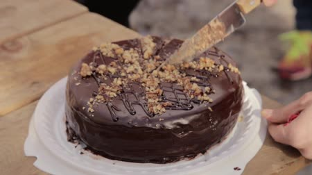 aprósütemény : Person cut the chocolate cake with a knife on a wooden table