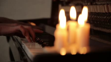 accompagnare : close-up femmine mani suonare pianoforte su un buio in una candela luce