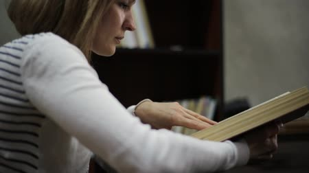 somente para adultos : young woman reading a big book in library. bookshelves with books