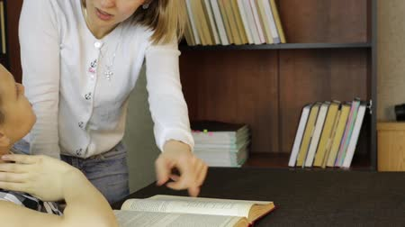 conflict : Young girl doing homework together with her mother. mom compels daughter to reads