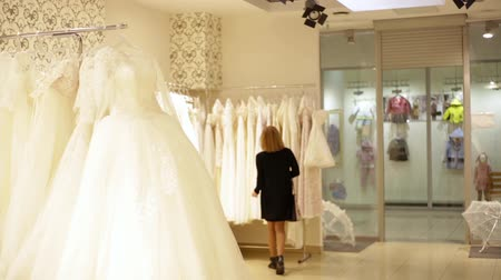 получать : young beautiful woman choosing a white gown in a wedding shop. Wed concept Стоковые видеозаписи