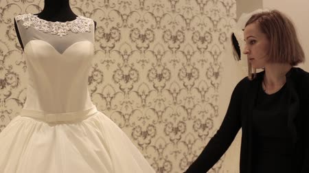 espartilho : close-up of dummy with wedding dress, young beautiful woman choosing a white gown in a wedding shop. Stock Footage