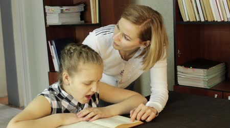unott : Mom helping her daughter do homework. schoolgirl makes lessons