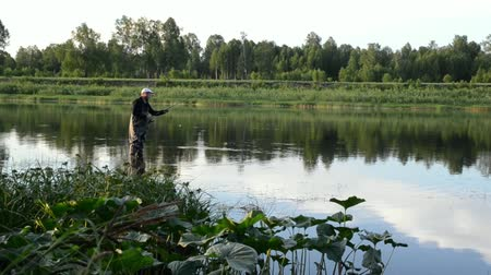 ryba : fisherman fishing in a calm river in the morning