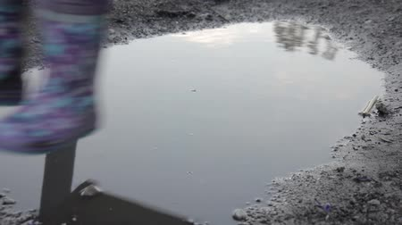 serra : Abandoned childrens playground, sad child swinging on a swing. reflection in puddles Stock Footage