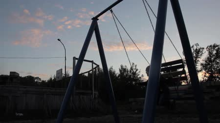 serra : sad child swinging on a swing on a dark sky background. child abuse, painful childhood