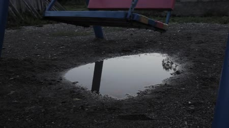 serra : Abandoned childrens playground, innocence sad child swinging on a swing. reflection in puddles.