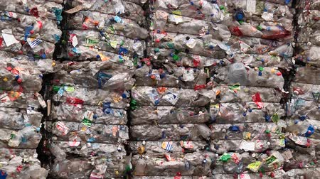 stacks : Piles of compressed plastic bottles prepared for recycling
