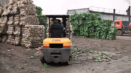 The forklift unloads the stack with extruded plastic bottles