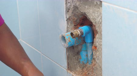 gips : The worker is plastering a wall with pipelines for water supply in a bathroom