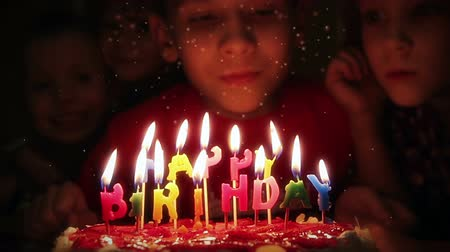 Boy blowing candles on birthday cake Stock mozgókép