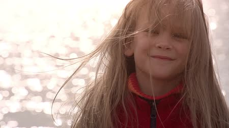 human eye : Girl 8 years old standing on the shore. Long blonde hair waves wind. Slow Motion 240 fps Stock Footage