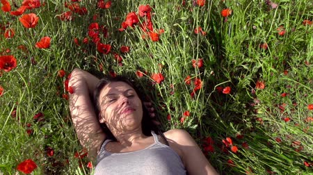 élvezet : The girl leans back among the poppies. Slow Motion at a rate of 480 fps