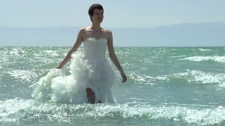 giydirmek : Bride in a wedding dress in the rolling surf. Slow Motion at a rate of 240 fps Stok Video