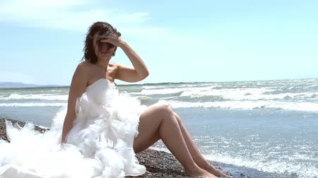 romantic : Beautiful brunette in a wedding dress sitting by the sea. Rolling waves touch the feet. Slow Motion at a rate of 240 fps