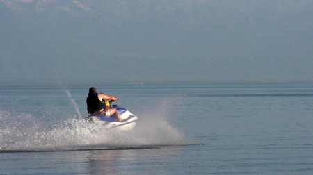 küçük sandal : The man rolls the small son on a jet ski.  Motion at a rate of 240 fps Stok Video