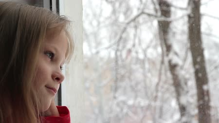 okno : Girl looking at snow flakes falling outside the window Wideo