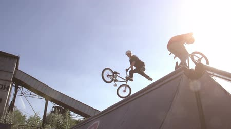 sport : Two young men perform stunts on bikes. Slow Motion at a rate of 240 fps
