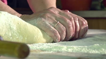 хлеб : Slow Motion at a rate of 240 fps. Womens hands knead the dough for homemade cake in the sun