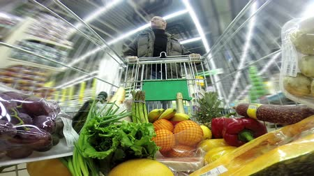 lökés : Timelapse. Man with a shopping trolley is moving rapidly between rows in a huge store Stock mozgókép
