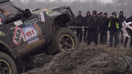ралли : International competition in autocross on the planet. Competitor rides through mud sports track. Behind the fence viewers are unidentified. Slow Motion at a rate of 240 fps