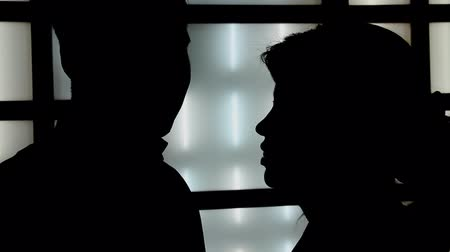 siluety : Silhouette couple on the background wall light. Occurs emotional conversation with hugs and kisses