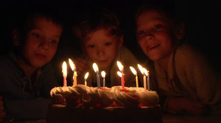 день рождения : Three children having fun blowing out candles on a birthday cake