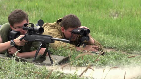 hedef : Sniper rifle with optical lying beside spotter which looks through binoculars. Slow Motion at a rate of 240 fps Stok Video