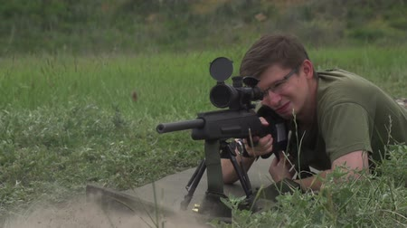 orvlövész : Sniper in camouflage and sunglasses shoots at a target. Slow Motion at a rate of 240 fps Stock mozgókép