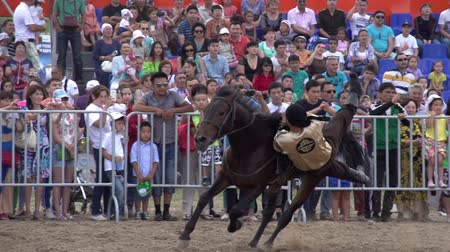 arquibancadas : Rider in national dress jumping on the background of bleachers filled with spectators. Slow Motion at a rate of 240 fps