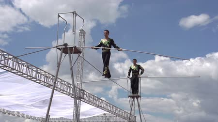 tightrope : Two tightrope walker demonstrate mastery on a sky background. Slow Motion at a rate of 240 fps