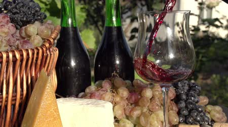pieces of cheese : In pouring a glass of wine on the background of a basket with grapes, wine bottles and pieces of cheese. Slow Motion at a rate of 240 fps