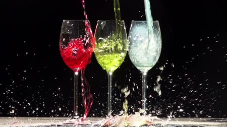 coquetel : Three glasses on a black background. In glasses pouring jet of different colors. Slow Motion at a rate of 240 fps Vídeos