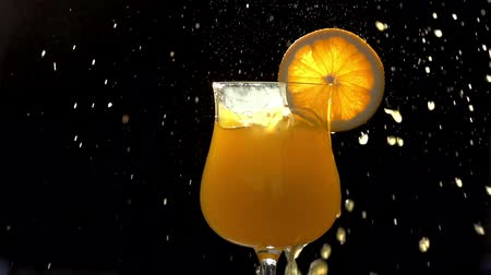 meyve suyu : Ice cubes falling into a glass of orange juice and a slice of orange. Fall creates many beautiful spray and foam. Slow Motion at a rate of 240 fps