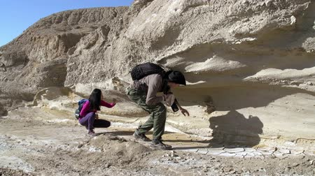 exploration : Two paleontologist considering fossils sticking out of the walls of the canyon