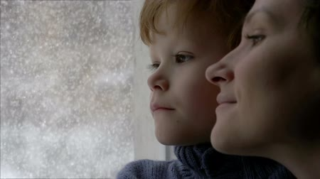 dech : Mother with young son looking out the window. Outside the window the snowstorm Dostupné videozáznamy